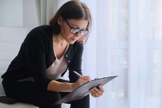 Age woman social worker, psychologist sitting near the window with clipping board