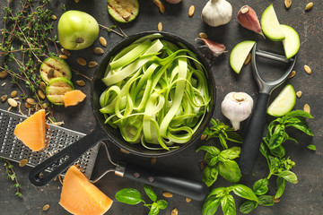 Frying pan with tasty zucchini pasta and ingredients on dark background