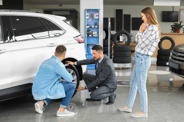 Couple buying new car in salon