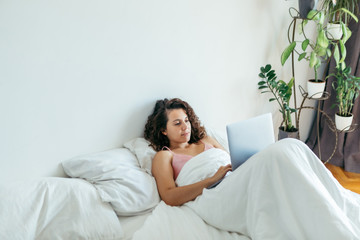 woman with laptop in bed freelancer