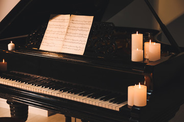 Stylish grand piano with burning candles in evening