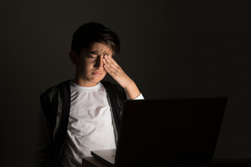 Portrait of a young boy rubbing his eyes while looking at his laptop. (Children)