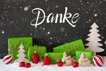 German Calligraphy Danke Means Thank You. Green Christmas Present With Decoration Like Tree And Ball. Black Background With Snowflakes