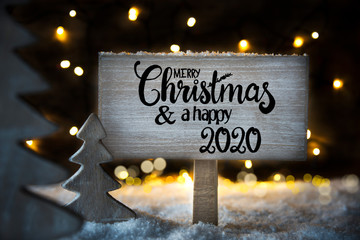 Sign With English Calligraphy Merry Christmas And A Happy 2020. Christmas Tree With Fairy Lights And Snow