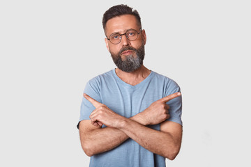 Close up portrait of Caucasian male points at different sides with index fingers, cant choose between two items, has calm expression, wearing glasses and gray t shirt, isolated over white background.