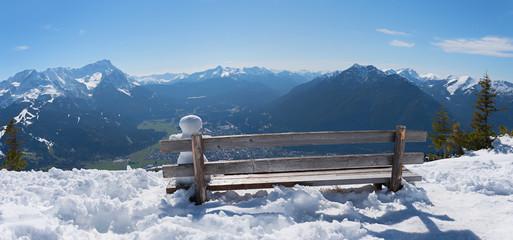 kleiner Schneemann sitzt auf einer Bank mit Blick nach Garmisch und die Zugspitze, Winterlandschaft
