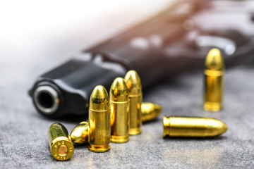 Gun with ammunition on stone background. 9 mm pistol gun weapon and bullets at table.