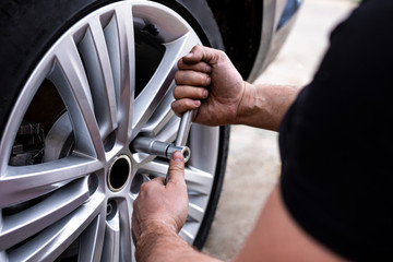 Picture of a man changing tires on the car