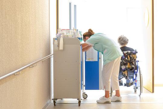 Aide soignante au travail accompagne personne agée en fauteuil roulant dans couloir hopital clinique maison de retraite