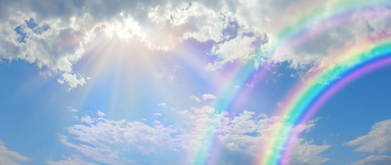 Beautiful vibrant double rainbow Cloudscape Background - awesome blue sky with pretty clouds, bright sun shining down and a large double rainbow arcing across the right corner with copy space Fotobehang