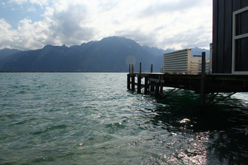 A wooden pier at a big lake with view on mountains. Location: Lake Geneva, Montreux, Switzerland