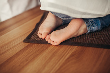 children's bare heels in jeans on a wooden floor with a brown plaid