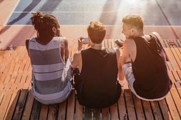 Three Men Sitting on the Bleachers