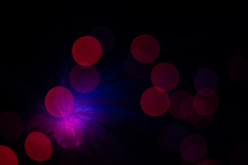 Colorful red, blue and pink lens flares with beautiful bokeh on black background