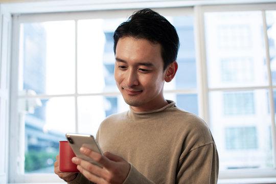 カップを持ちスマホを操作する30代男性
