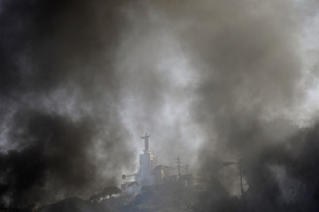 Smoke rises from burning tires as Christ Roi Convent is seen at the background on the highway at Nahr El Kalb