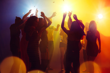 Holidays. A crowd of people in silhouette raises their hands on dancefloor on neon light background. Night life, club, music, dance, motion, youth. Yellow-blue colors and moving girls and boys.