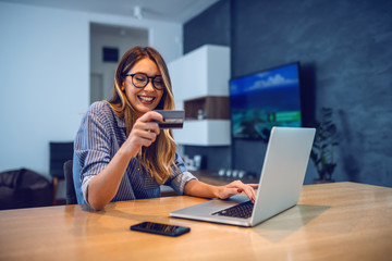Young attractive smiling Caucasian woman with eyeglasses holding credit card and typing number of her bank account on laptop while sitting at dining table. Online shopping concept.