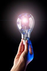 Light bulb in hand in front of black background. Technology or idea concept