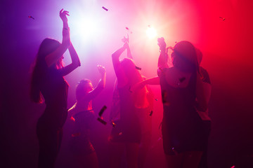 Celebrating. A crowd of people in silhouette raises their hands on dancefloor on neon light...