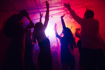 Catching moment. A crowd of people in silhouette raises their hands on dancefloor on neon light...