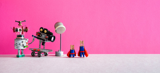 Comical art. Toy robot cameraman makes a movie about super heroes. Funny clothespin actors, robotic operator, camcorder spotlight. Filmmaking behind the scenes concept. Pink background, empty space