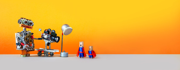 Comical art. Toy robot cameraman makes a movie about super heroes. Funny clothespin actors, robotic operator, camcorder spotlight. Filmmaking behind the scenes concept. Yellow background, empty space