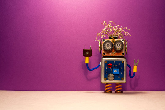 Funny steampunk robotic toy on purple background. Kind funny robot with crazy hairstyle and raised up by hand. copy space