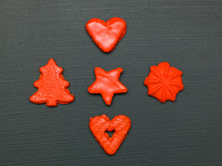 red christmas cookies on black background from above
