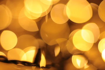 Defocused lights of warm shade, festive background. Christmas garland out of focus.