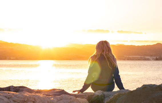lonely girl sitting back to camera on stone sea bay waterfront shore line and enjoy by beautiful bright orange sunset light with colorful glares , thinking and human emotion concept photography