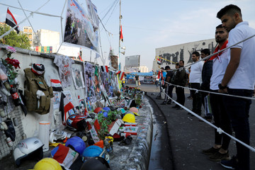 Iraqi demonstrators look at the pictures and items of demonstrators who were killed during the ongoing anti-government protests in Baghdad