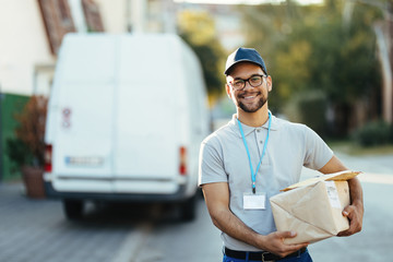 Portrait of young happy courier with packages for a delivery.
