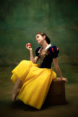 Young ballet dancer as a Snow White with poisoned apple in forest. Flexible caucasian ballerina...