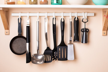 Different kitchen utensils hanging on wall with home decors