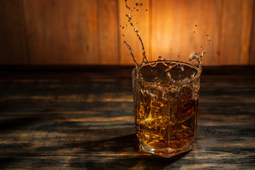 glass of whiskey with spray on a wooden table in a bar Fototapete