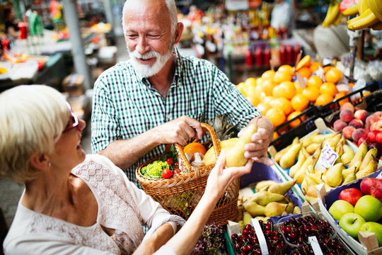 Mature shopping couple with basket on the market. Healthy diet.