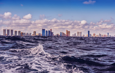 Fotobehang -   View of skyscrapers away from the ocean. Waves in the foreground and city silhouettes on the horizon. USA. Florida. Miami