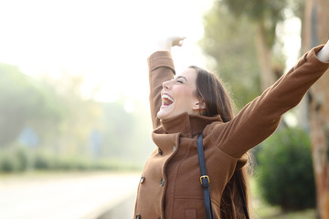 Excited woman celebrating success in winter
