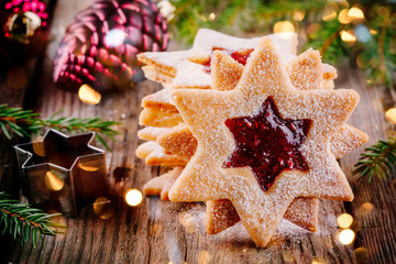 Linzer Christmas cookies filled with raspberry jam on wooden background.
