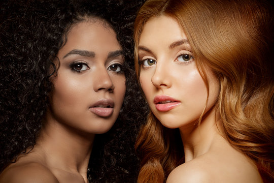 Multi-ethnic beauty. Caucasian and African. Different ethnicity women on black background. Beautiful vogue girls.