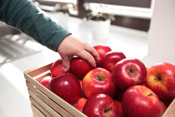 The child is taking the juicy red apple from the basket with apples