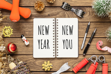 New year resolutions or goals for healthy lifestyle, lose weight and join gym concept. New Year New You written in notebook with dumbbells, jump ropes and Christmas ornaments decorations.