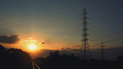 Pictures of electrical transportation through high voltage poles during sunrise time. Electric power transportation concept