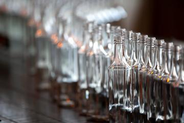 Glassworks. Glass industry. Many glass bottles on a factory conveyor.