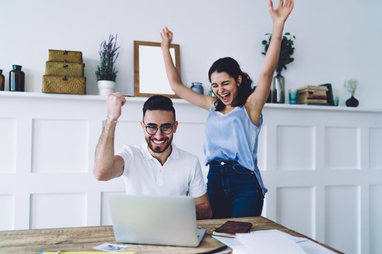 Young happy couple smiling with look of success and looking at laptop