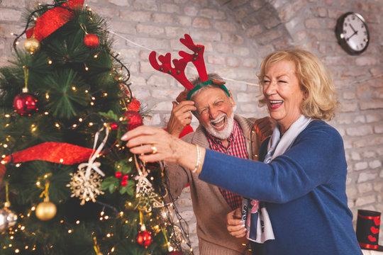 Senior couple having fun while decorating Christmas tree