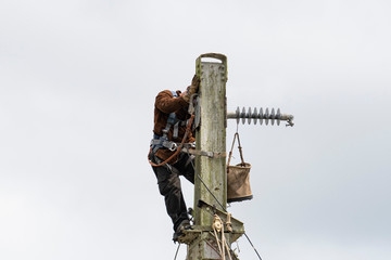 View of a man working on welding on top of an iron railroad tower
