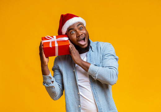Crazy black guy in Santa hat holding Christmas gift box