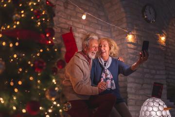 Senior couple taking a selfie on Christmas Eve